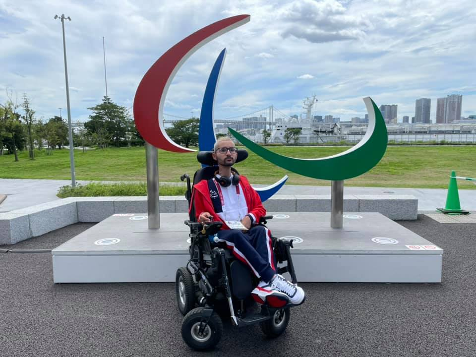 Photographie de Samir Vanderbeken devant le symbole des Jeux paralympiques de Tokyo.
