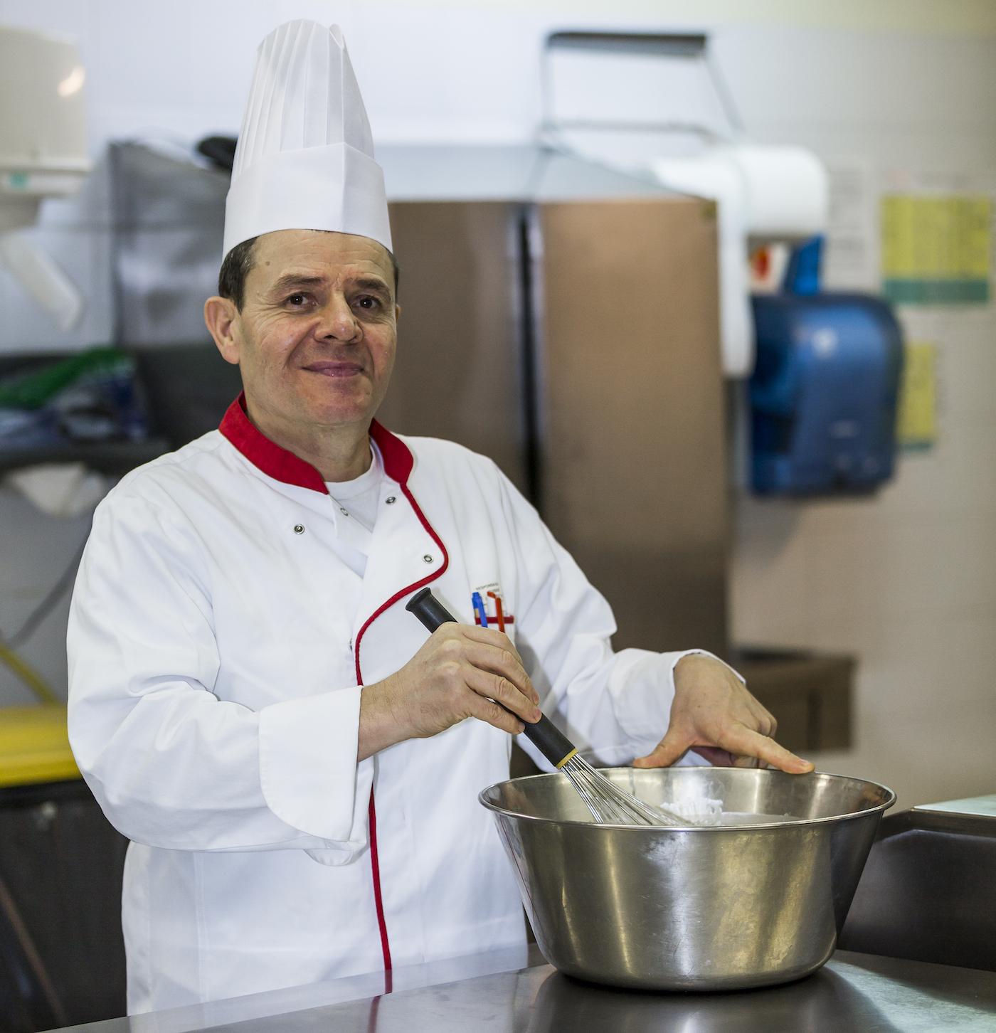 Le cuisinier fouette une préparation.