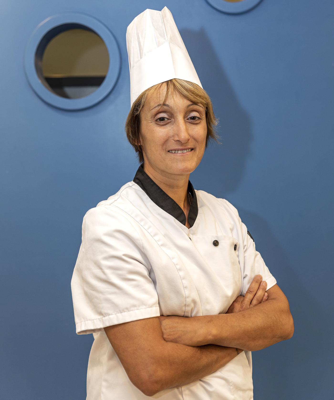 La cuisinière pose pour le photographe.