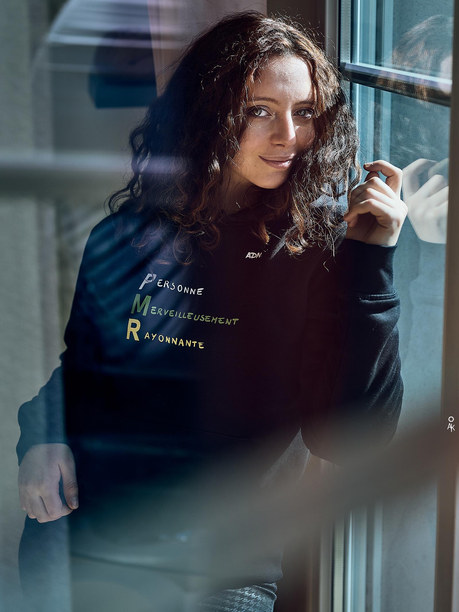 Une femme portant un T-shirt avec l'inscription Personne Merveilleusement Rayonnante (PMR)