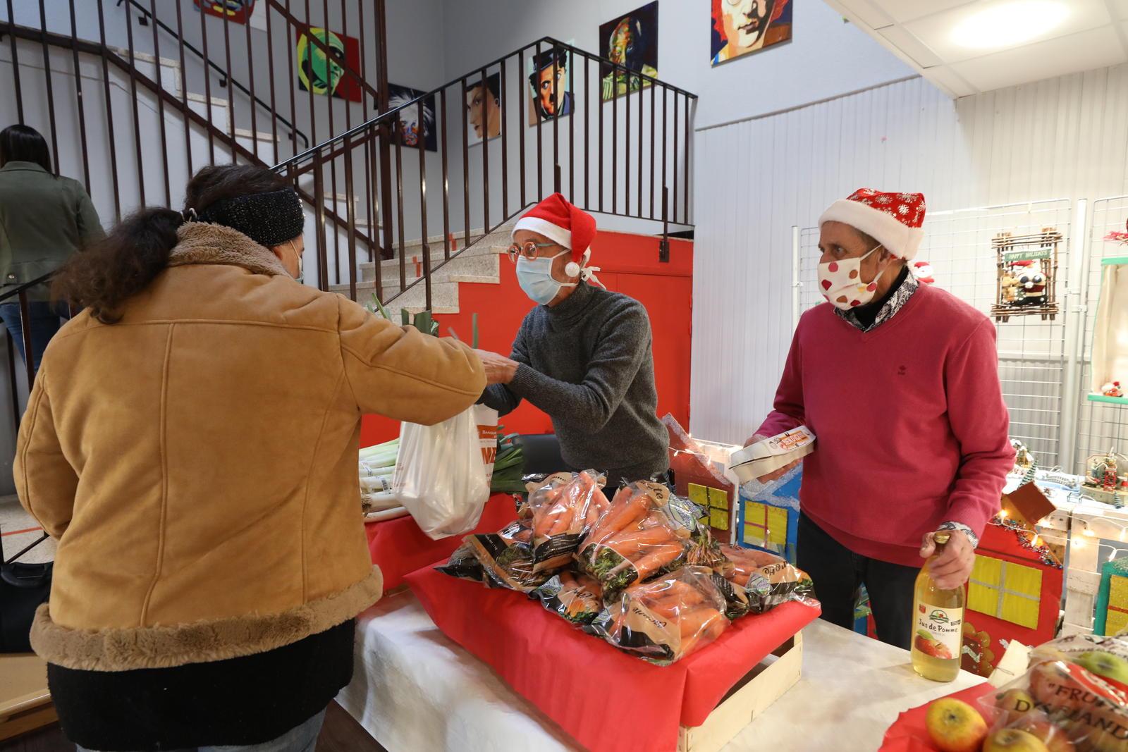 Des personnes portant un bonnet de Noël distribuant des produits locaux