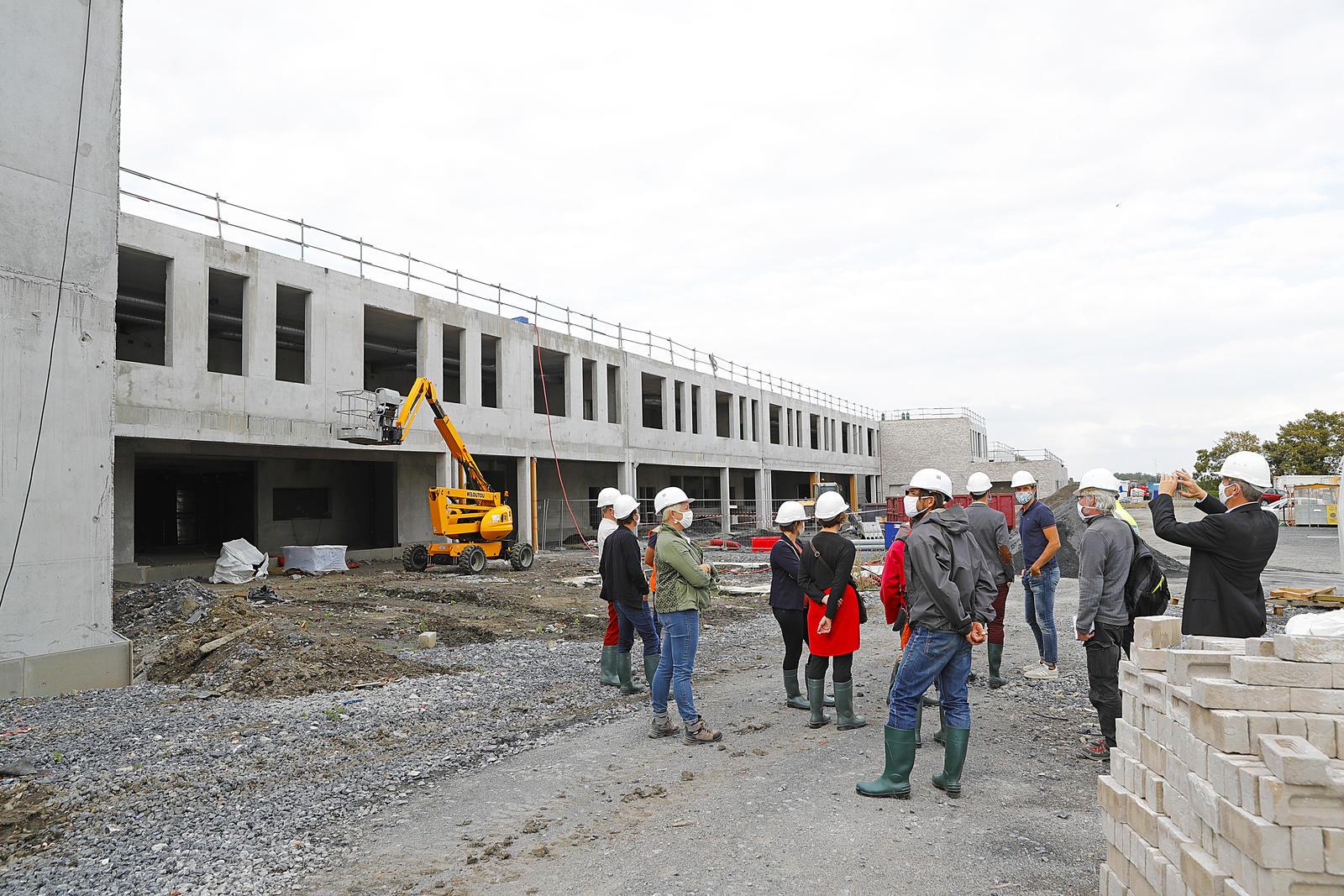 Un groupe de personnes devant un bâtiment en chantier